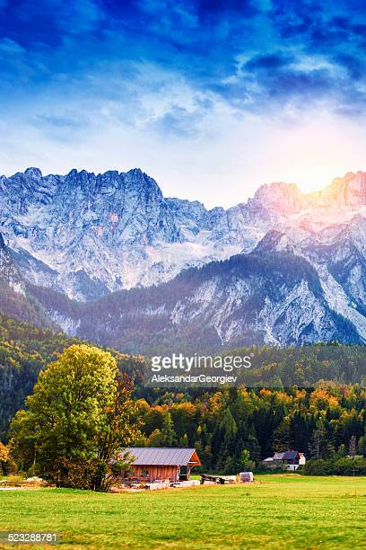 Traditional Wooden Alpine Chalet Autumn at Sunset and Snowy Mountains