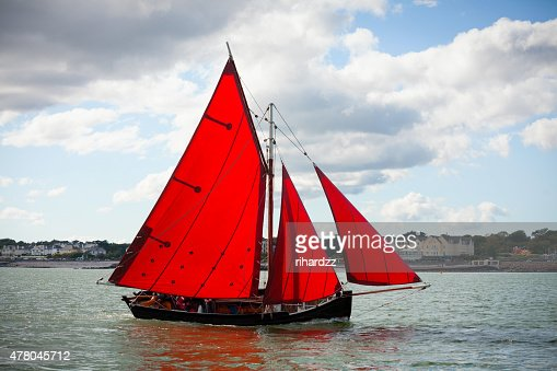 Traditional wooden boats with read sail. : Stock Photo