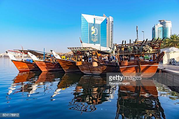 Traditional wooden dhows contrast with modern buildings in Dubai