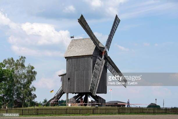 Traditional Wooden Windmill On Field Against Sky