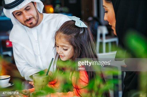 Tradicional árabe joven familia disfrutando en Café