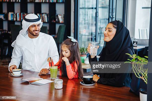 Traditional Young Arab family enjoying at cafe