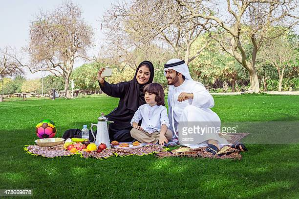 Traditional Young Arabian family taking selfie at park