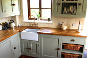 Photo showing a traditional country kitchen, with a large range cooker with gas hob, duck egg green cupboards and wall cabinets, a white ceramic sink (Belfast sink), a terracotta tiled floor, wooden w
