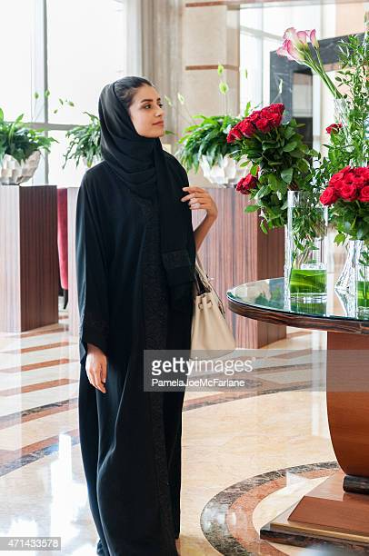 Traditionally Dressed Arabian Woman Walking by Flowers in Hotel Lobby
