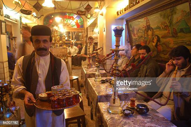 A traditionally dressed chaychi with a tray of tea glasses at the Azari teahouse in south Tehran Iran 24th March 2004 Behind him customers drink tea...