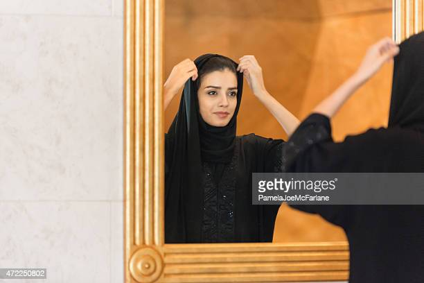 Traditionally Dressed Emirati Woman Adjusting Hijab in Gold Framed Mirror