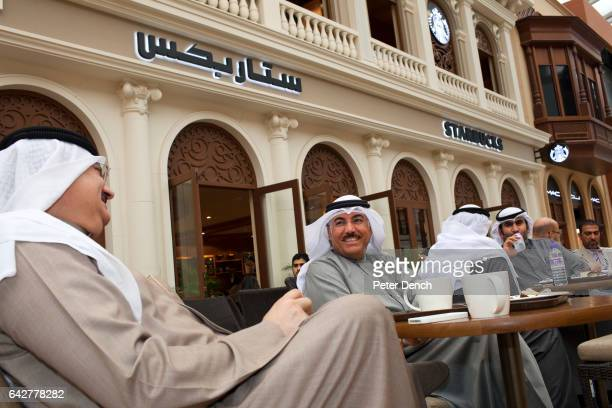 Traditionally dressed Kuwaiti men drink coffee outside Starbucks on the Mall of the Avenues in Kuwait City The Mall of the Avenues id the largest...