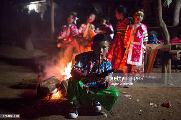 Traditionally dressed Lahu children gather around a fire before taking part in New Year's dancing The boy in front holds a small instrument made from...