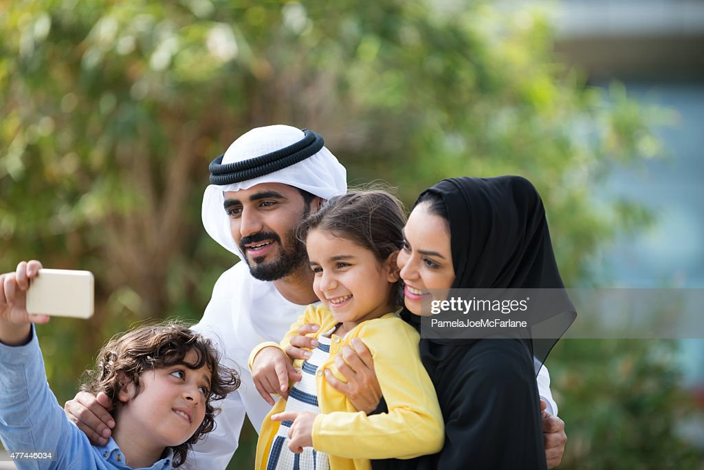 Traditionally Dressed Middle Eastern Family Posing for Selfie in Park