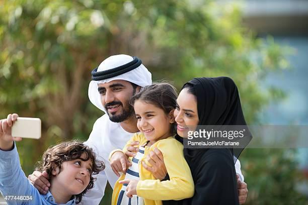 Traditionnellement vêtus du Moyen-Orient en famille posant pour un Selfie dans le parc