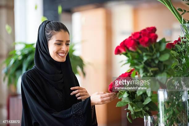 Tradicionalmente vestido de Medio Oriente mujer tocando Red Roses en un florero