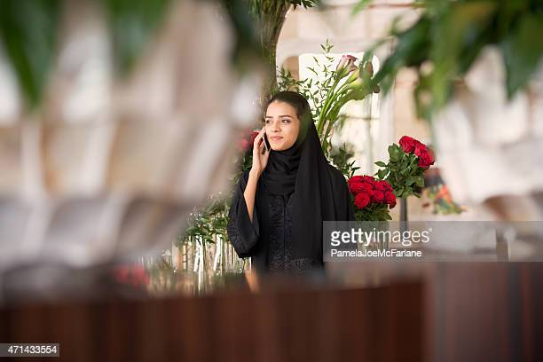Traditionally Dressed Middle Eastern Woman with Flowers Talking on Cellphone