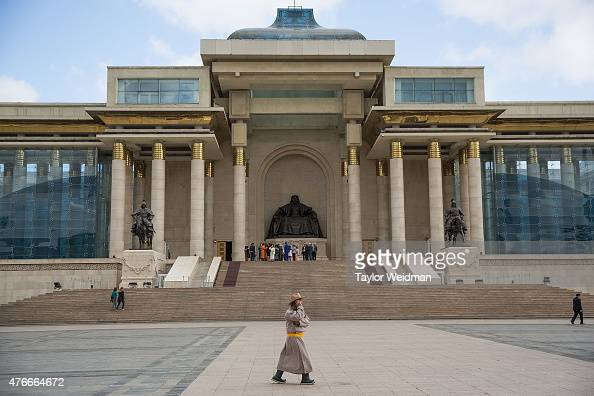 A traditionally dressed Mongolian man talks on a mobile phone in front of a statue of Chinggis Khan on June 11 2015 in Ulaanbaatar Mongolia A few...