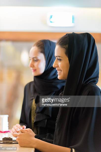 Traditionally Dressed Smiling Young Middle Eastern Women Standing at Counter