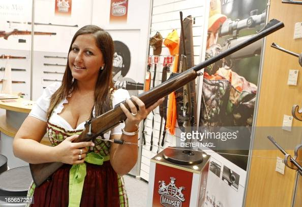 Traditionally dressed young Austrian Caroline Zatschkowitsch poses with a Mauser boltaction rifle at the 'Jaspowa' hunting fair on April 5 2013 in...