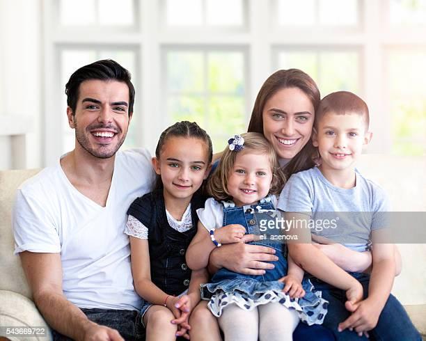Traditionnelle cinq Portrait de famille, assis sur le canapé à la maison.