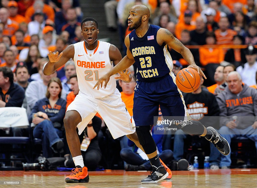 Trae Golden #23 of the Georgia Tech Yellow Jackets controls the ball against the defense of Tyler Roberson #21 of the Syracuse Orange during the second half at the Carrier Dome on March 4, 2014 in Syracuse, New York. Georgia Tech defeated Syracuse 67-62.