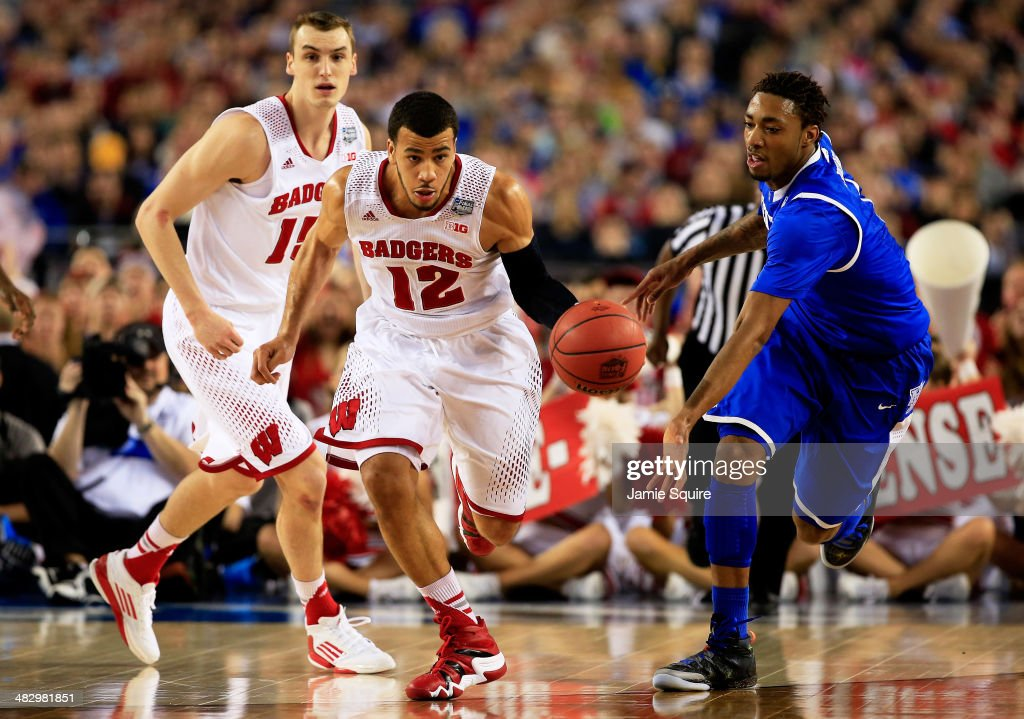 Traevon Jackson of the Wisconsin Badgers brings the ball up the floor as James Young of the Kentucky Wildcats defends during the NCAA Men's Final...