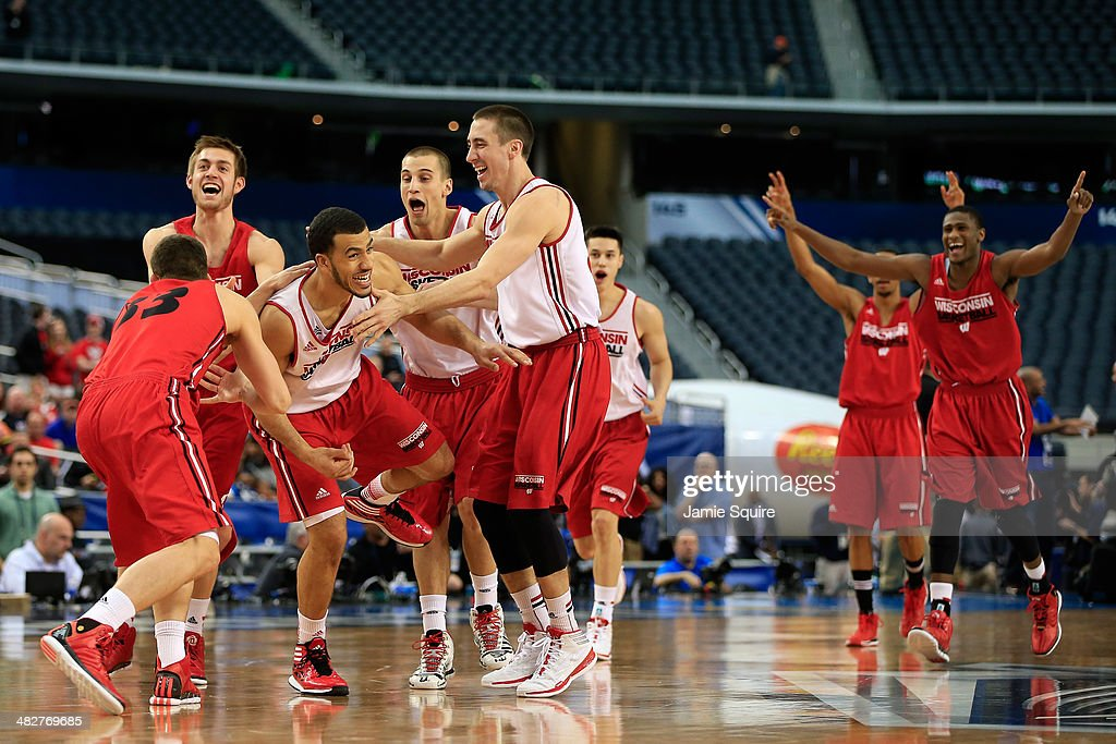 Traevon Jackson of the Wisconsin Badgers celebrates with his teammates after making a half court shot as the Badgers practice ahead of the 2014 NCAA...