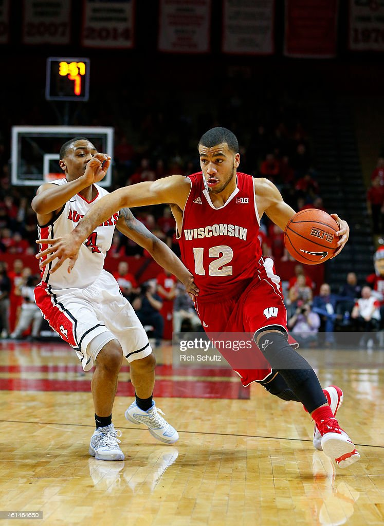 Traevon Jackson of the Wisconsin Badgers dribbles the ball past Myles Mack of the Rutgers Scarlet Knights during the first half of a college...