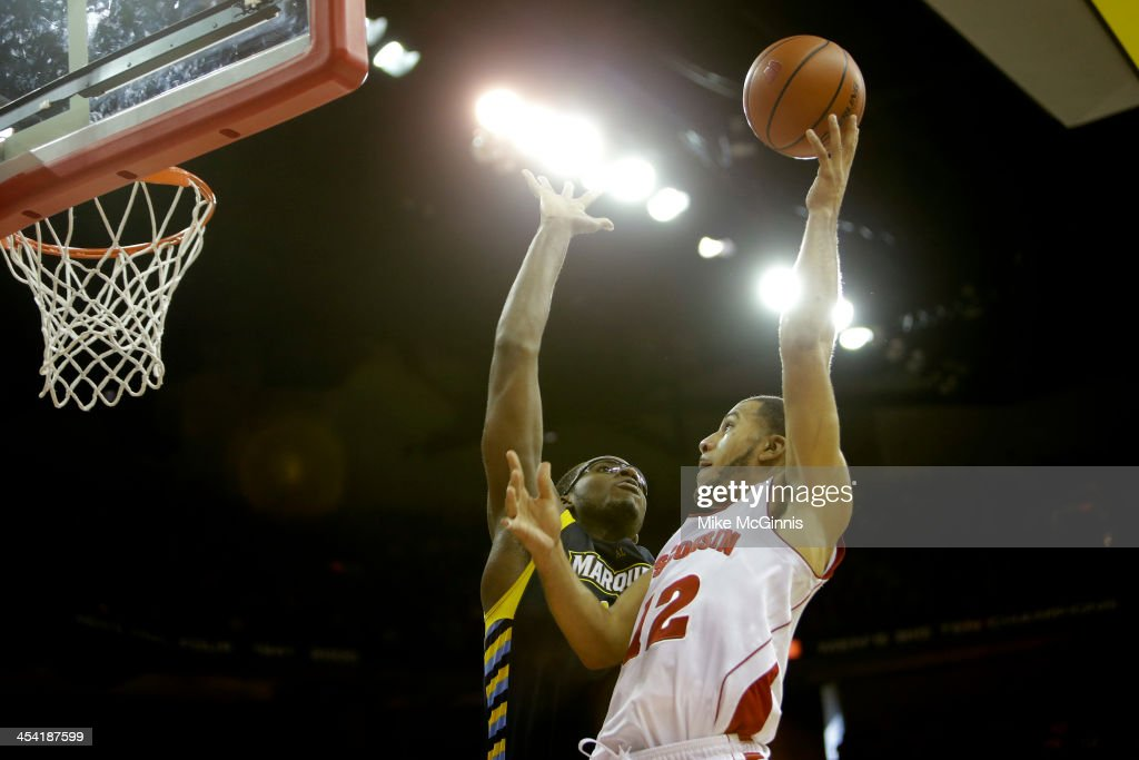 Traevon Jackson #12 of the Wisconsin Badgers drives to the hoop with Chris Otule #42 of the Marquette Golden Eagles defending during the second half at Kohl Center on December 07, 2013 in Madison, Wisconsin.