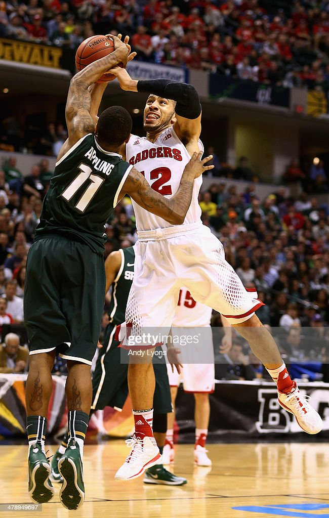 Traevon Jackson of the Wisconsin Badgers is fouled by Keith Appling of the Michigan State Spartans during the second half of the Big Ten Basketball...
