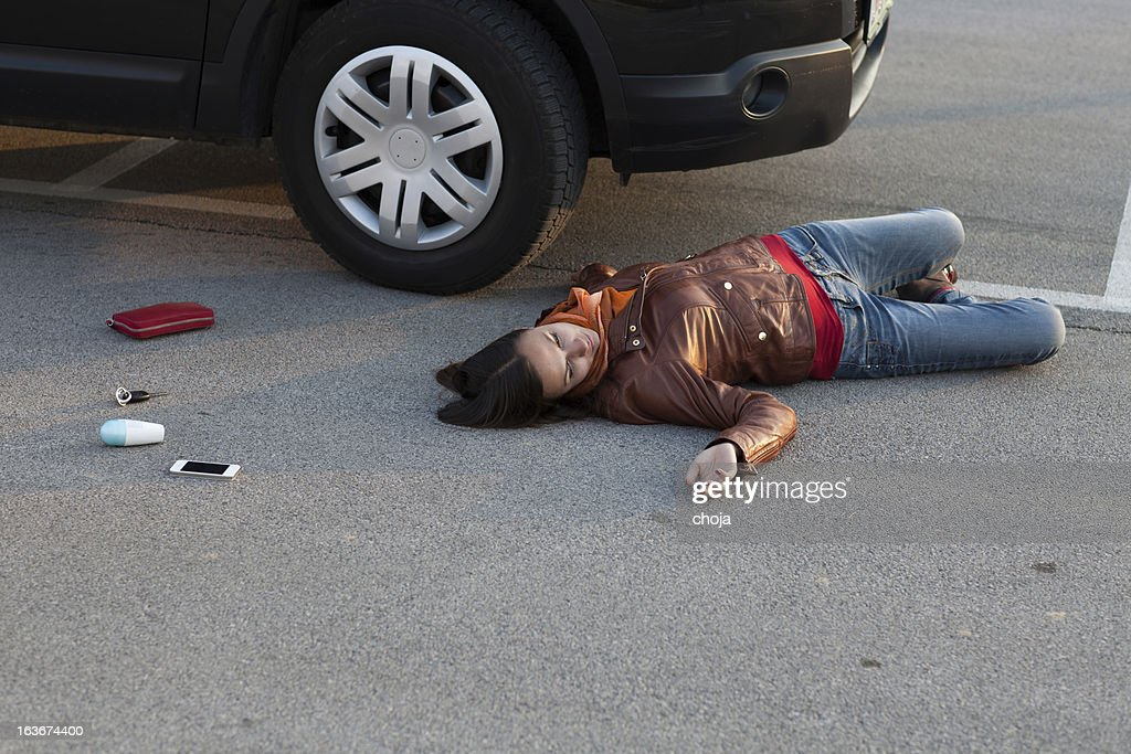 Traffic accident..young woman hit by a car : Stock Photo