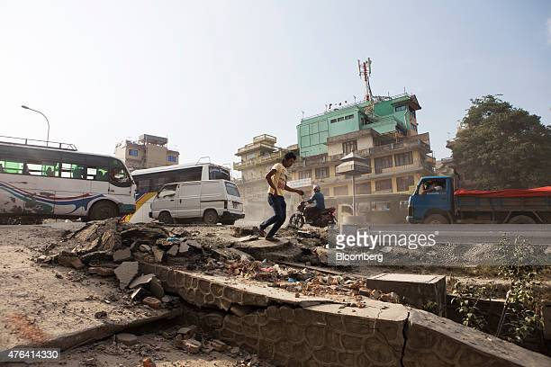 Traffic and a pedestrian pass a section of earthquakedamaged road in Kathmandu Nepal on Wednesday June 3 2015 Nepal's gross domestic product will...