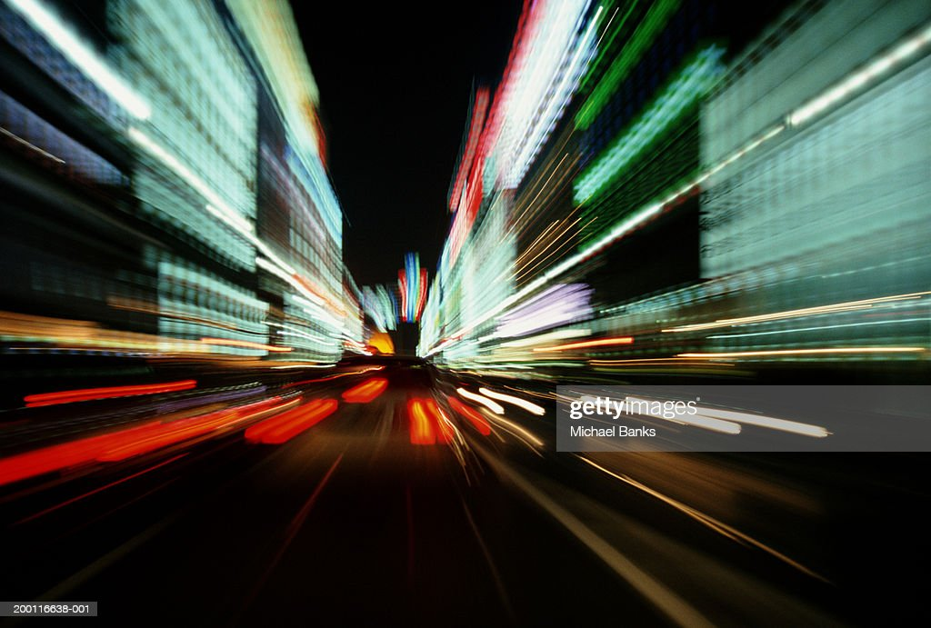 Traffic and illuminated buildings on street, night (long exposure) : Stock Photo
