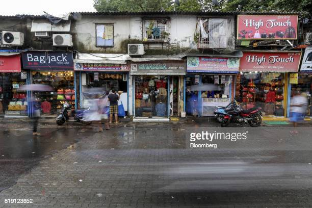 Traffic and pedestrians with umbrellas walk past leather goods stores in the Dharavi area of Mumbai India on Tuesday July 18 2017 India's new goods...