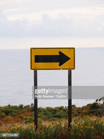 Traffic Arrow Sign Against Sea