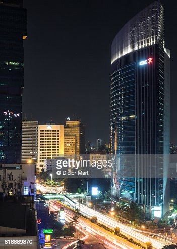 Traffic at night in Jakarta business district : Stock Photo
