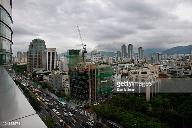 Traffic builds up near a small park in downtown Daegu backdropped by mountains and skyscrapers on August 26 2011 in Daegu South Korea Daegu is South...