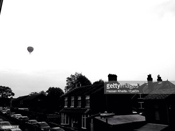 Traffic By Buildings Against Clear Sky With Hot Air Balloon