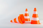 A traffic cone lying on its side next to two standing traffic cones