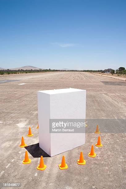Traffic cones around white box