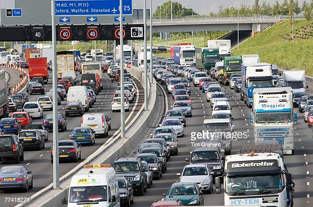 Traffic congestion cars and trucks travelling in both directions on M25 motorway London United Kingdom