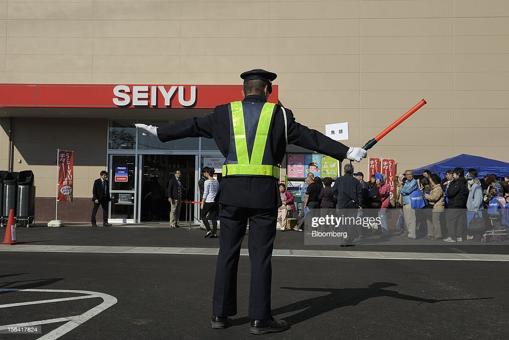 A traffic controller works in front of a Seiyu GK supermarket in Tokyo, Japan, on Wednesday, Nov. 14, 2012. Seiyu GK is a unit of Wal-Mart Stores Inc. Photographer: Akio Kon/Bloomberg via Getty Images