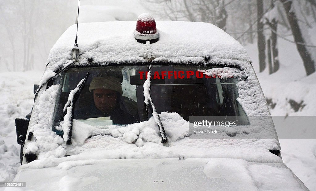 A traffic cop along with his officer inspect the condition of highway and stranded vehicles amid heavy snowfall on December 14, 2012, in Banihal, 110 km (68 miles) south of Srinagar, the summer capital of Indian Administered Kashmir, India. Most parts of the Kashmir Valley, including Srinagar, received fresh snowfall, leading to closure of the 300 km (188 miles) Jammu-Srinagar Highway, the only road link between Kashmir and rest of India. Project Beacon authorities of the Border Roads Organisation, that maintains the highway, had already started efforts to clear the highway for traffic. The number of vehicles stranded on the highway was being ascertained.