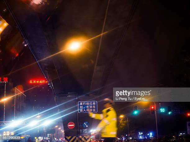 Traffic Cop On Illuminated Street At Night