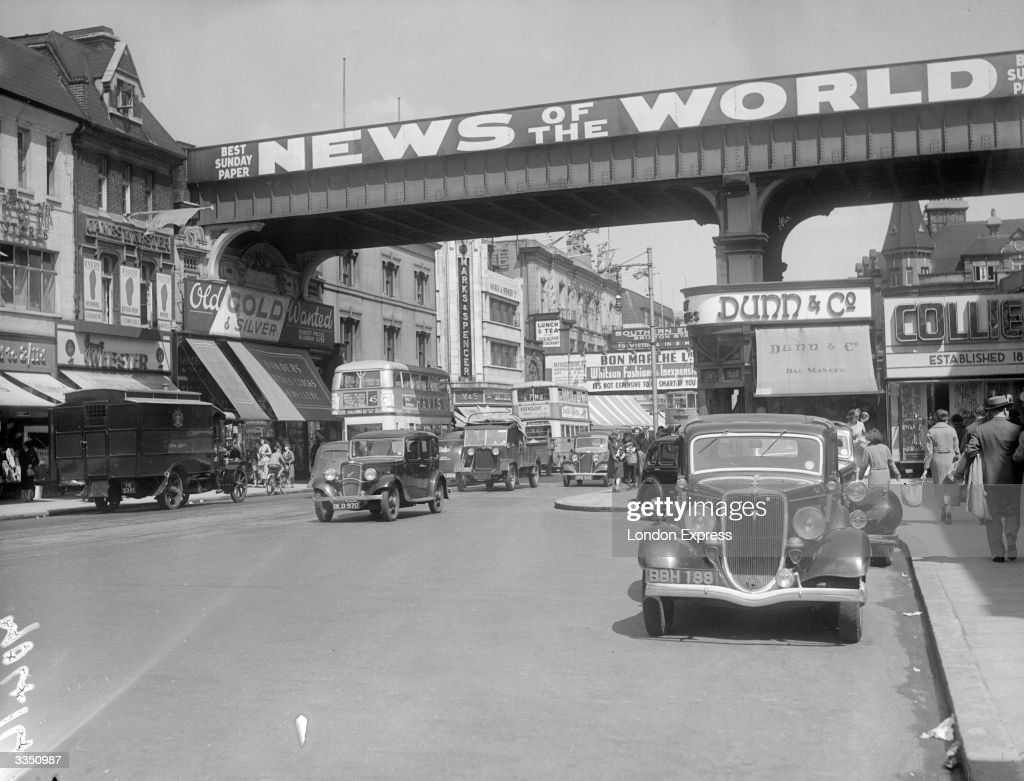 Traffic in Brixton High Street, south London, spanned by a railway bridge on which the newspaper News of the World is prominently advertised.