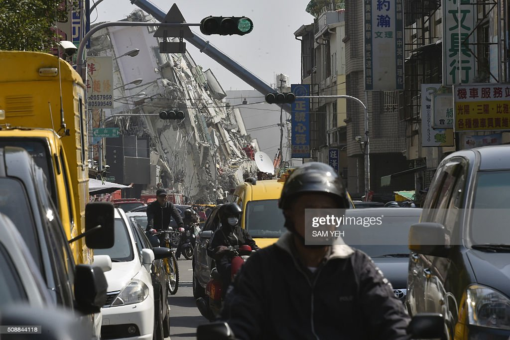 Traffic is seen past the collapsed Wei Kuan complex building on the second day of rescue operations following a 6.4 magnitude earthquake in southern Taiwan's city of Tainan on February 7, 2016. Rescuers raced against time February 7 to free more than 100 people buried beneath the rubble of apartment blocks felled by an earthquake in southern Taiwan that left 19 dead, as an investigation was launched into the building collapse. AFP PHOTO / Sam Yeh / AFP / SAM YEH