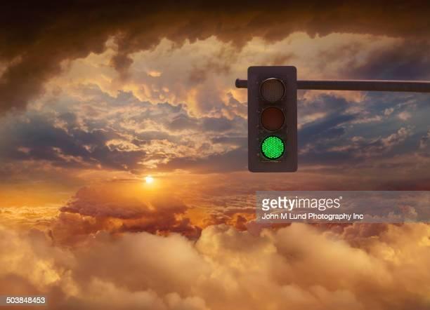 Traffic light in sunset sky