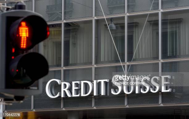 A traffic light is seen in front of a sign of Swiss bank Credit Suisse on June 11 2013 in Basel AFP PHOTO / FABRICE COFFRINI