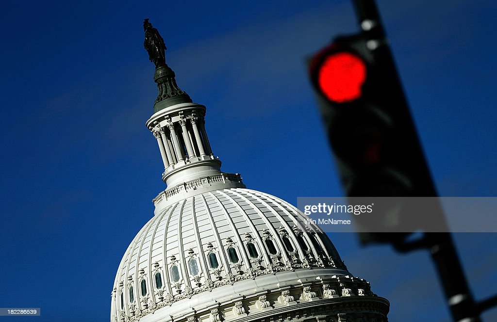 A traffic light is seen in front of the United States Capitol building as Congress remains gridlocked over legislation to continue funding the...