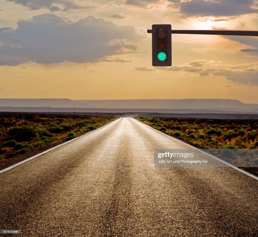 Traffic light on rural road in desert landscape