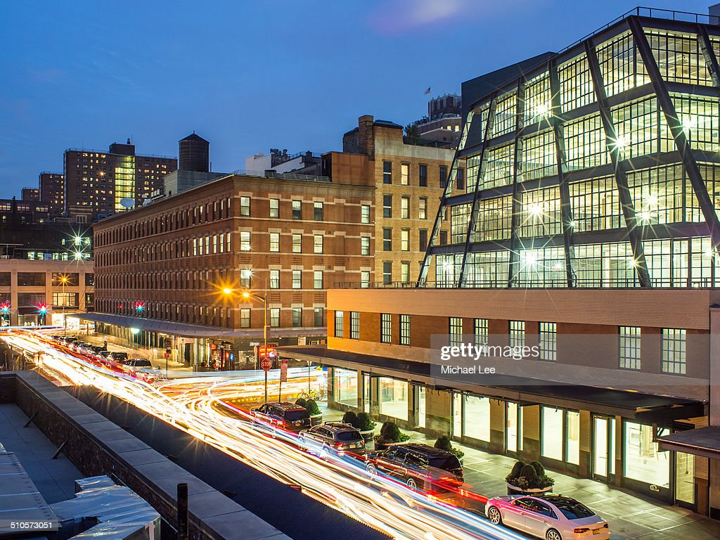 Traffic light trails show the busy nature of this street in the Meat Packing District during the evening in New York City