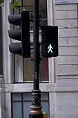 Traffic light with green man lit up at pedestrian crossing, building in background.
