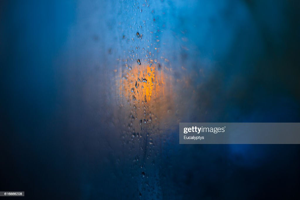 Traffic lights reflected in glass in rain : Stock Photo
